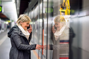 Beautiful senior woman standing at the underground platform, waiting, entering the train, talking on the phone