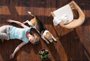 Beautiful senior woman with her dog at home, lying on wooden terrace, relaxing