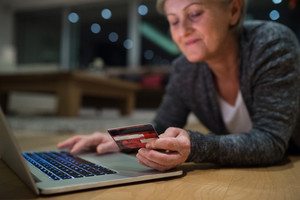 Beautiful senior woman with laptop at home in her living room lying on the floor, holding a credit card, shopping online