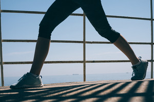 Beautiful slender legs of a young athletic woman in blue sneakers against the background of the sea in the morning light close-up. Concept of a healthy lifestyle.