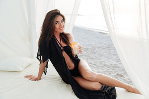 Beautiful slim brunette girl posing in swimsuit with long hair sitting on beach bed at the seashore and drinking cocktail
