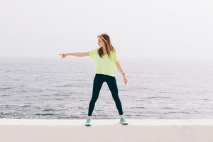 Beautiful slim girl in green sportswear shows the direction of the hand on the background of the sea, wide angle shooting.