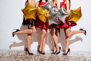 Beautiful slim legs of young women with star shaped balloons and confetti standing and having party over white background