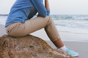 Beautiful slim woman sitting on a rock by the sea. She is dressed in beige trousers and a denim shirt. Side view.