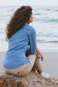 Beautiful slim woman with curly hair sitting on a rock by the sea. She is dressed in beige trousers and a denim shirt. Back view.