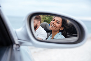 Beautiful smiling woman looking at her reflection in a car mirror
