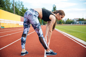 Beautiful sports woman doing stretching exercise on outdoor stadium