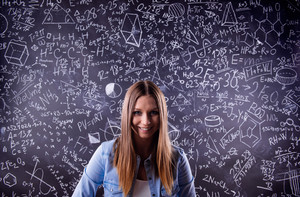 Beautiful student in blue denim shirt against big blackboard with mathematical symbols and formulas. Studio shot on black background.