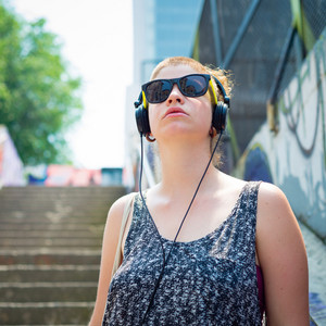 beautiful stylish modern young woman listening to music in the city