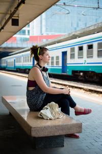 beautiful stylish modern young woman waiting train at the station