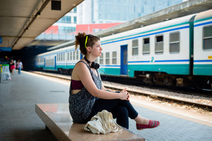 beautiful stylish modern young woman waiting train at the station