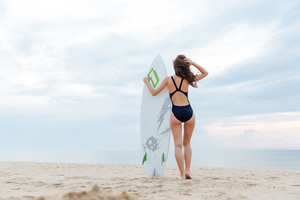 Beautiful surfer girl standing on the beach with her surfboard on a sunny day