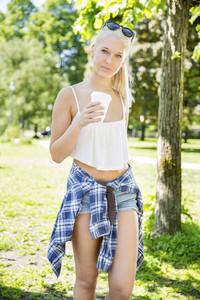 Beautiful teenage girl drinking coffee in park