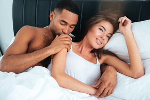 Beautiful tender multiethnic young couple lying in bed