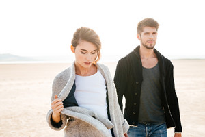Beautiful woman and handsome man walking along seaside in autumn
