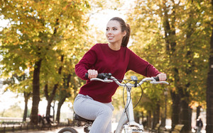 Beautiful woman dressed in sweater walking with her bicycle outdoors. Look aside.