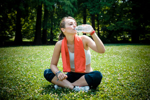 beautiful woman fitness drinking water at the park