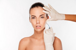 Beautiful woman gets an injection in her face isolated on white background