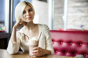 Beautiful Woman Having Hot Chocolate With Cream In Cafe