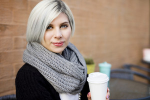 Beautiful Woman Holding Coffee Cup At Sidewalk Cafe