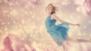 Beautiful woman in a blue dress flying in a pink peony flower fantasy
