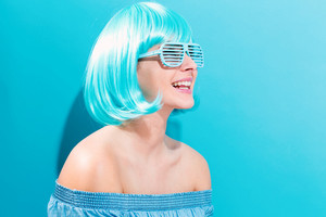 Beautiful woman in a bright blue wig on a blue background
