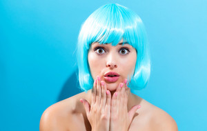 Beautiful woman in a bright blue wig on a pink background