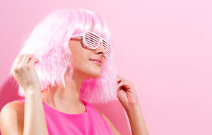 Beautiful woman in a bright pink wig on a pink background