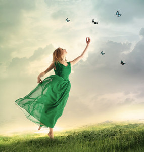 Beautiful woman in a green dress chasing butterflies on a mountain