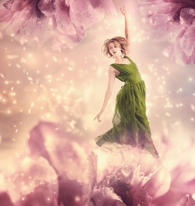 Beautiful woman in a green dress jumping in a pink peony flower fantasy