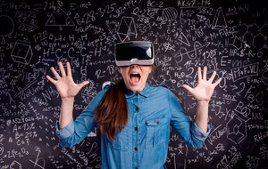Beautiful woman in blue denim shirt wearing virtual reality goggles, screaming, scared. Student against big blackboard with mathematical symbols and formulas. Studio shot on black background.
