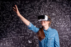 Beautiful woman in blue denim shirt wearing virtual reality goggles, stretching arms. Student against big blackboard with mathematical symbols and formulas. Studio shot on black background.