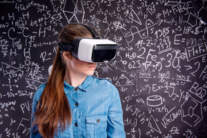 Beautiful woman in blue denim shirt wearing virtual reality goggles. Student against big blackboard with mathematical symbols and formulas. Studio shot on black background.