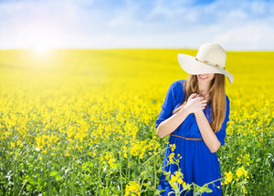Beautiful woman in blue dress in summer canola field.