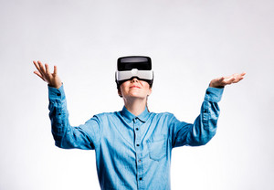 Beautiful woman in denim shirt wearing virtual reality goggles stretching arms. Studio shot on gray background