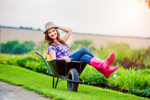 Beautiful woman in rubber boots and hat sitting in wheelbarrow in sunny green garden