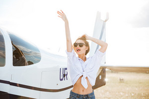 Beautiful woman in sunglasses posing near a plane outside