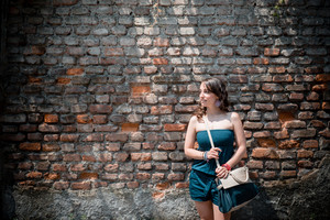 beautiful woman in the city on a brick wall