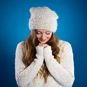 Beautiful woman in warm sweater on blue background
