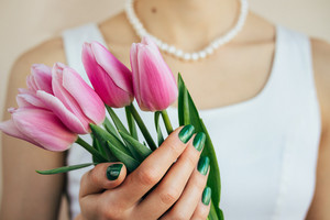 Beautiful woman in white dress and pearl necklace holding a pink tulips, close-up