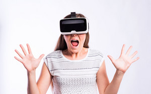 Beautiful woman in white t-shirt wearing virtual reality goggles, mouth open, shocked, screaming, shouting. Studio shot on gray background