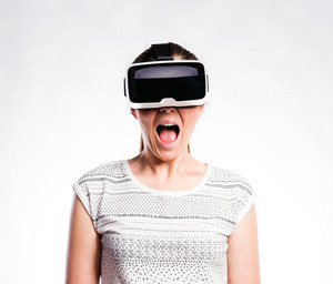 Beautiful woman in white t-shirt wearing virtual reality goggles, mouth open, shocked. Studio shot on gray background