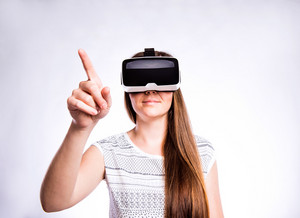 Beautiful woman in white t-shirt wearing virtual reality goggles reaching up. Studio shot on gray background