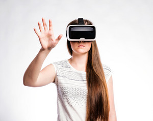 Beautiful woman in white t-shirt wearing virtual reality goggles stretching arms. Studio shot on gray background