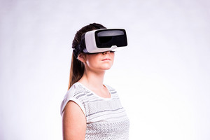 Beautiful woman in white t-shirt wearing virtual reality goggles. Studio shot on gray background