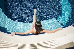 Beautiful woman is swimming in blue swimming pool.