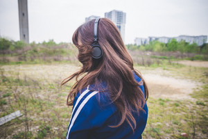 beautiful woman listening music in a desolate lurban landscape