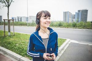 美しい女性は、荒涼とした田園風景で音楽を聴いて