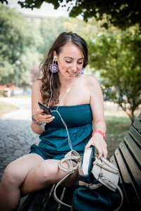 beautiful woman listening to music with phone player in the city