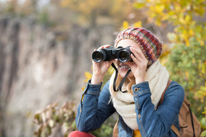 Beautiful woman looking through binoculars against colorful autumn forest